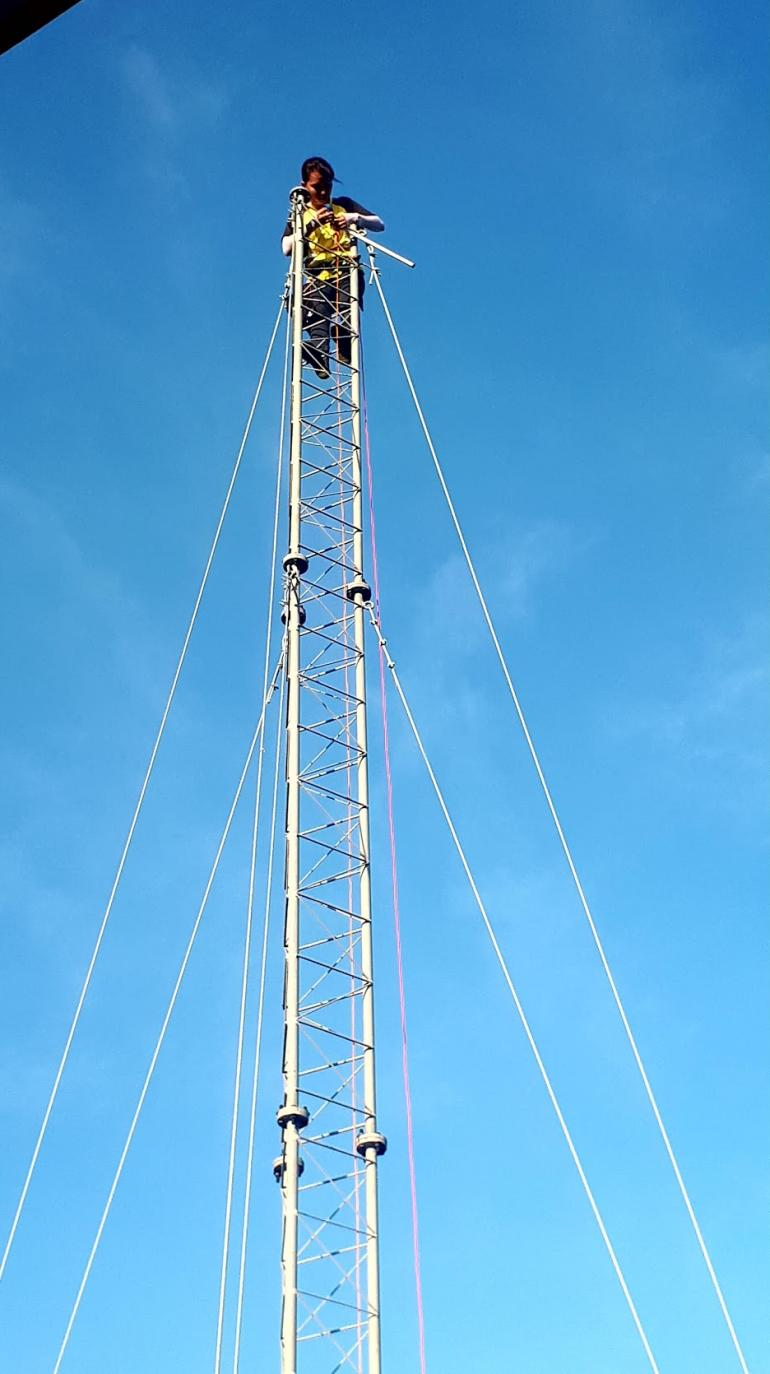 A person high up on a communicatiaons tower