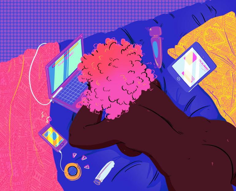 Image description: Woman on bed looking at laptop, dildo and other sex toys nearby