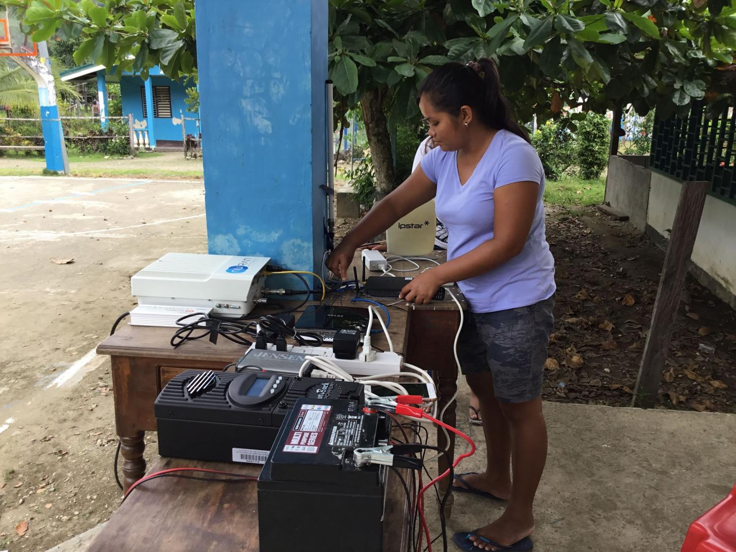A woman setting up network cables on a table