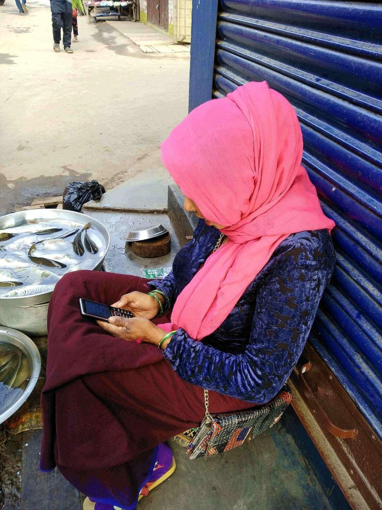Image description: woman with mobile phone seated outside shop