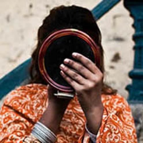 Image description: Woman's face shielded from view by circular mirror-like object