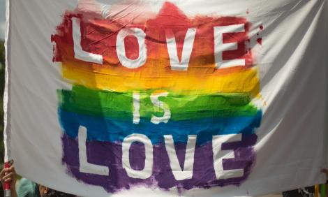 Banner saying Love is Love on rainbow background