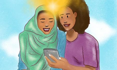 Two african women looking a mobile phone together