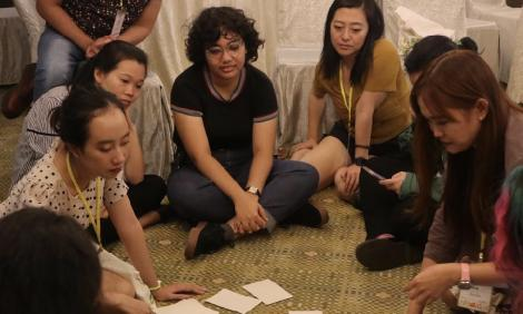 Image description: Women and girls sitting on floor