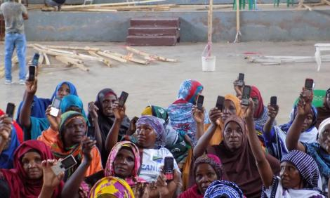 Image description: Photo of women holding up basic mobile phones