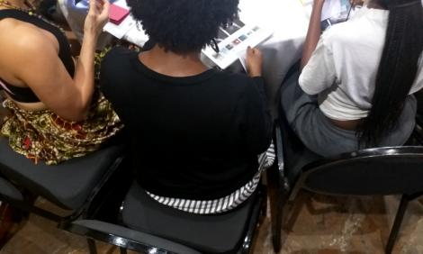 A group of African women making collage art around a table