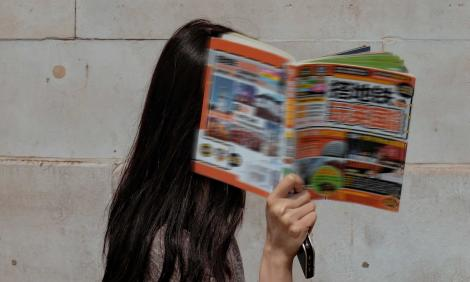 Image description: woman walking by, covering her face with Chinese magazine