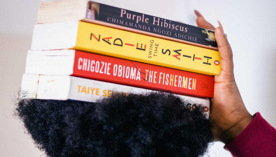 Image description: Books by women authors balanced on a person's head