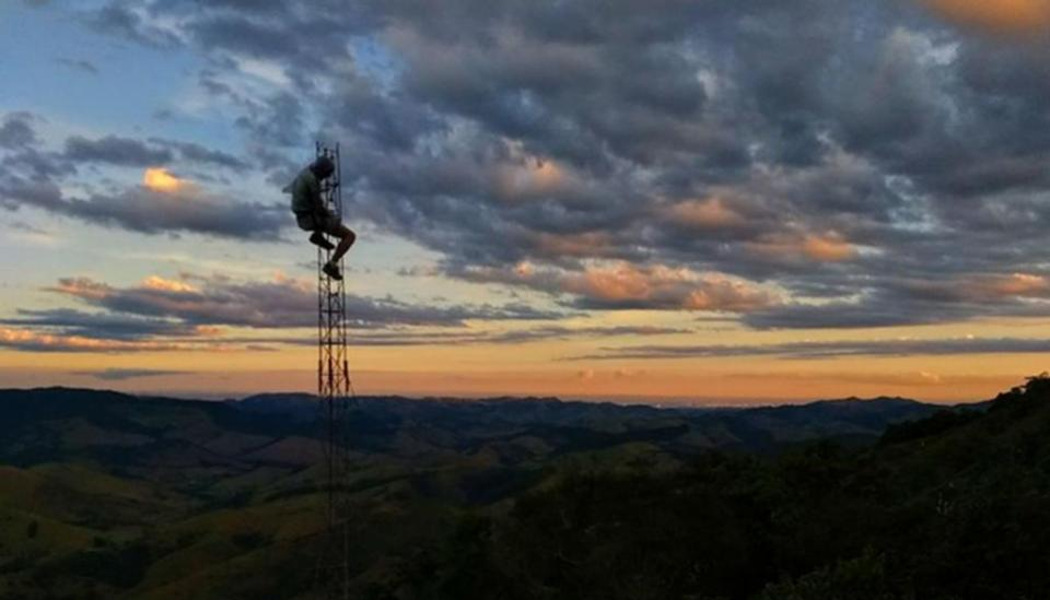 Image description: A lone body high on communications tower against view of sunrise and clouds