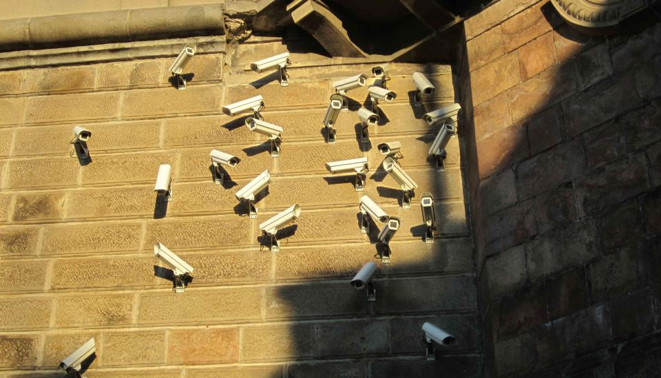 Image description: Numerous surveillance cameras on a wall