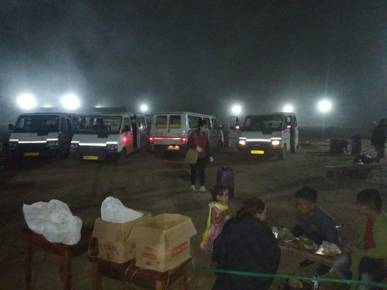 Returnees at bus stand in Manipur at night.