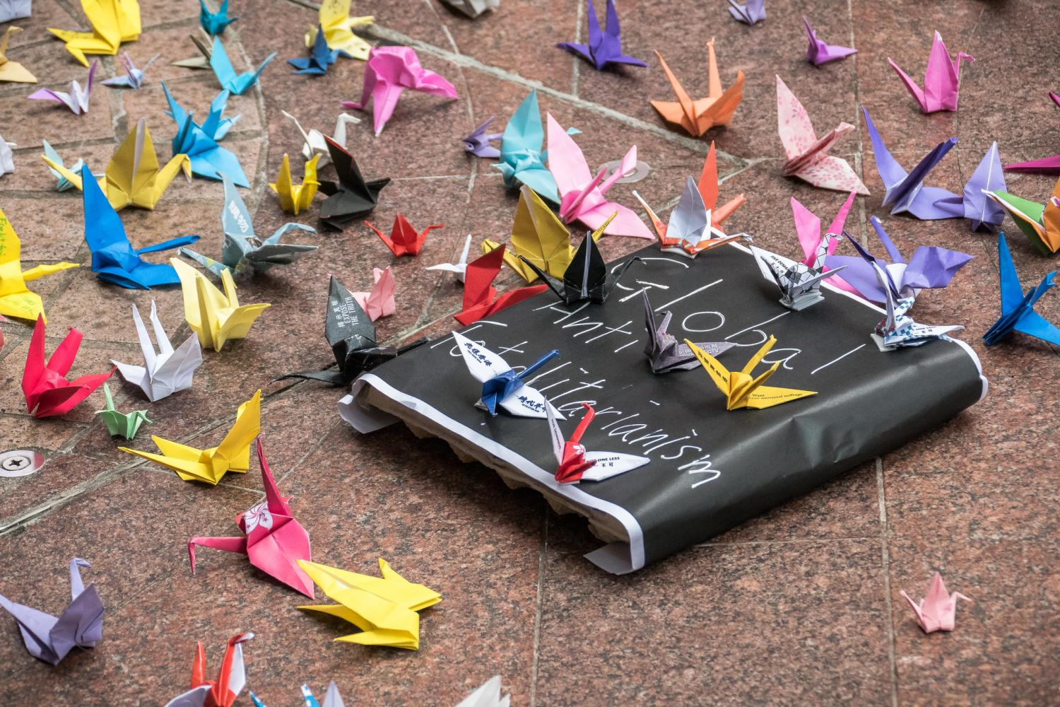 Paper cranes on text Global anti-totalitarianism